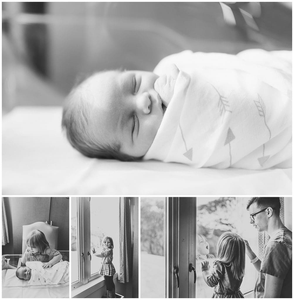 Newborn baby boy laying in hospital bassinet and sister looking down over him dad and sister looking out hospital window