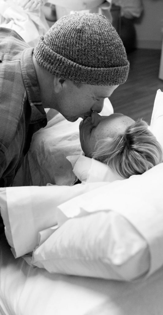 Birth Photography, husband leaning down to kiss wife
